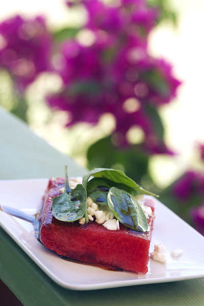 grilled watermelon, baby spinach, vinaigrette and goat cheese on white plate