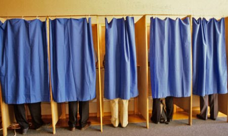 people voting behind curtains at polling booths